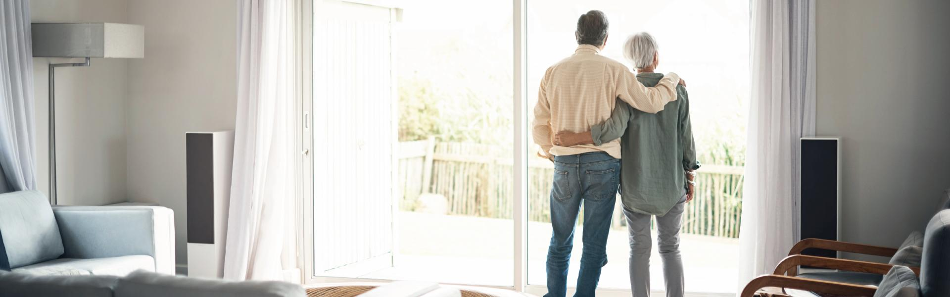 retired couple looking out patio door